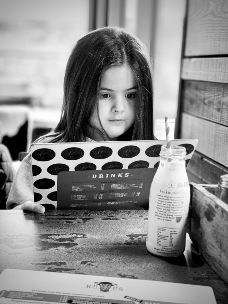 Little Girl Reading Menu in Burger Bar